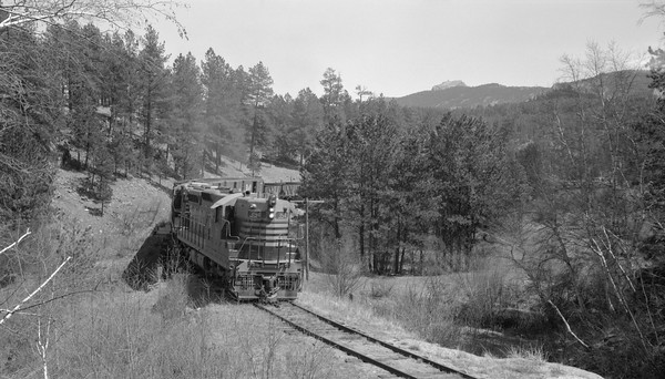 2018.15.N69.7497--ed wilkommen 116 neg--CB&Q--EMD diesel locomotive 354 on freight train in Black Hills--location unknown--no date