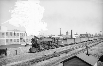 2018.15.N68F.4968--ed wilkommen 6x9 neg--CMStP&P--steam locomotive 4-6-4 F6 129 on passenger train 18 Columbian passing Washington St tower--Milwaukee WI--no date