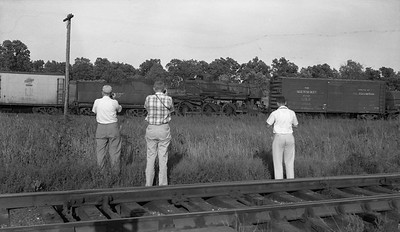 2018.15.N59.1980F--ed wilkommen 116 neg--NRHS CNS&M fantrip--NRHS fans photgraphing passing C&NW freight train with retired 4-6-0 R-1 steam locomotive--North Chicago IL--1955 0905. Engine is 168 (2nd), early R-1 built by Baldwin. Renumbered from 1042 to make room for diesel numbers. Burned in Clintonville, WI enginehouse fire. Sold for scrap to Hyman-Michaels 9/27/1955.