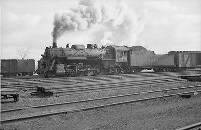 2018.15.N87.6403F--ed wilkommen 6x9 neg--ICRR--steam locomotive 2-8-2 1214 on freight train in yard action--location unknown--no date