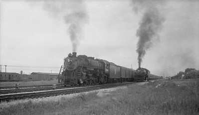 2018.15.N92.7736--ed wilkommen 116 neg--SOO--steam locomotive 4-8-2 N-20 4015 on passenger train passing light engine in siding--location unknown--no date