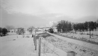 2018.15.N92.7734--ed wilkommen 116 neg--SOO--steam locomotive on passenger train in snow action--location unknown--no date