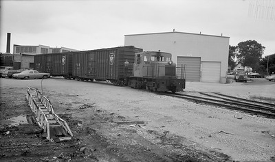 2018.15.N64.8266--ed wilkommen 116 neg--Municipality of East Troy--GE diesel locomotive switching freight cars on Trent Tube spur--East Troy WI--c1970 0000