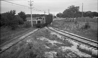 2018.15.N64.8267--ed wilkommen 116 neg--Municipality of East Troy--GE diesel locomotive with freight cars--East Troy WI--c1970 0000
