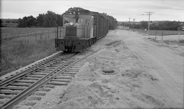 2018.15.N64.8264--ed wilkommen 116 neg--Municipality of East Troy--GE diesel locomotive with freight cars--East Troy WI--c1970 0000