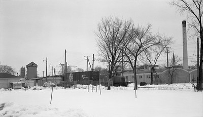 2018.15.N64.8815--ed wilkommen 116 neg--Municipality of East Troy--GE diesel locomotive switching lumberyard industry scene--East Troy WI--c1970