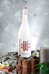 Alcohol bottle with plant, scarf, daisies, candle, chocolate on a wooden piece on grungy and glass background, side view.