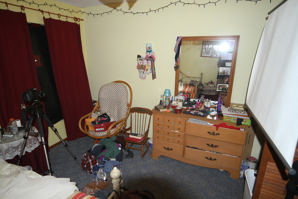 "This is a view of Allyson's bedroom showing the set up.  The window at the left is blocked off with black plastic film, with a 1/2"" hole, to permit light to enter the room.  The camera at the left, is mounted on a tripod to facilitate the slow shutter speed (20-30 seconds) required for the exposure.  A screen is hanging on the closet door approximately 10 feet from the window to project the image on."
