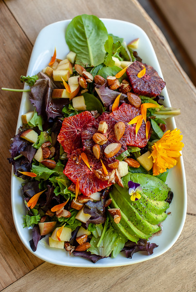 seasonal Farm salad with Bee Love Farms greens, candied almonds, blood oranges, apples, avocado, edible flowers and a house made elderberry vinaigrette.