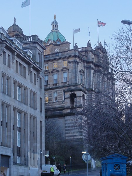 Bank of Scotland.<br><br>The building on the left is part of the Motel One, with room 711 in the top right corner with the flag. Building with dome on top: Bank of Scotland