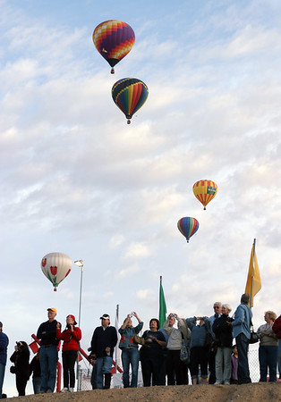 Spectators from near & far watch as the morning ascent balloons drift off into the horizon.