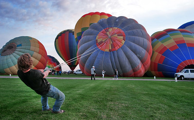 A young tender steadying a balloon for AM fill.  This particular canopy is one of the families oldest and the tender mentioned this may be it's last fiesta before retirement. With the cost of a standard balloon rig ranging from $30,000-$100's of thousands of dollars, not including chase vehicles, crew and travel costs, the ABQ Balloon Fiesta requires some serious cash to participate.