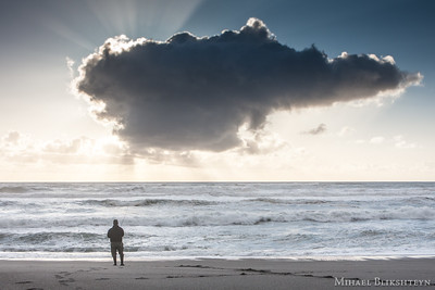 Surfperch fisherman on the beach at sunset under a cloud