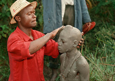 Mud from the sacred river is formed into a headdress with a young blade of grass pressed into it. Later the headdress is removed indicating that he is no longer a boy, but has become a man.