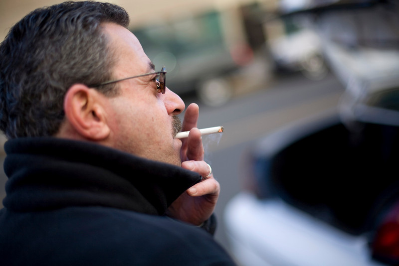 12/6/07 Boston, MA -- Fred Meister smokes outside his taxi and discusses Hackney rules and regulations with Boston Globe columnist Alex Beam Thursday December 6, 2007.  Erik Jacobs for the Boston Globe