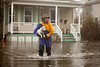 "3/15/10 Winchester, MA -- Emily Bushnell evacuates her dog Wally from her home (in background) during flooding along Forest Street in WInchester, Mass March 15, 2010.  ""I have lived here for 25 years and we have had five 100-year storms,"" Bushnell said."