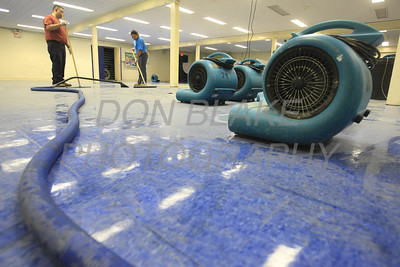 Workers squeegee water and use dryers to clean the  lunchroom which was under a foot of water from Hurricane Irene at St. Peter the Apostle School in New Castle, Del., Monday, August 29, 2011. The Dialog/Don Blake