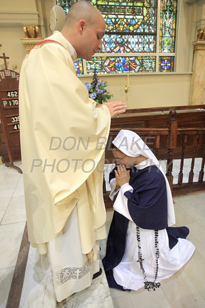 Fr. John Solomon blesses sister Sr. Gianna Maria Solomon, SV after his Ordination at the Cathedral of St. Peter, Wilmington, Del., Saturday, June 18, 2011. The Dialog/Don Blake