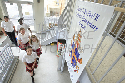 Seventh grade students Sophia Elliott (front), Allison Schemm, Sheila Hendrickson, Mikyhial Clarke, and Eric Acevedo walk by the schools banner at Pope John Paul II School in Wilmington, Del., April 13, 2011. The Dialog