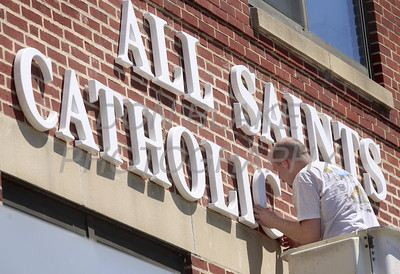 Dan Simpson from Tupp Sign Company installs the All Saints Catholic School sign on the front of the school in Elsmere, Del., Wednesday, August 17, 2011. All Saints Catholic School was formed to combined 3 schools with low attendance and had to be close in the spring. Over 500 students from the 3 schools will attending the new school in the fall. The Dialog/Don Blake