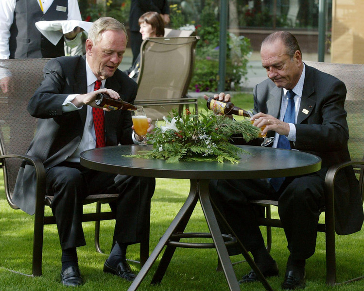 Prime Minister Jean Chretien and French President Jacques Chirac pour themselves a locally-brewed beer during an informal meeting Tuesday, June 25, 2002, at the G8 Summit retreat in Kananaskis, Alberta. (CP PHOTO/Fred Chartrand)