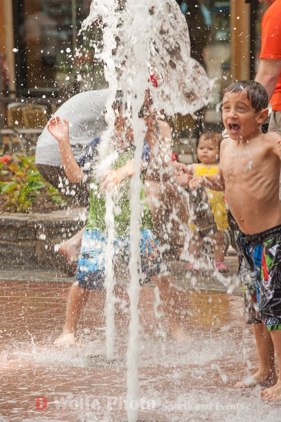 Zak, a five year old from Montgomery County is in awe of how much fun the water jets are to play in on a hot day.