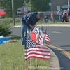 An patriot placing flags along the parade route to honor all military services and their members.