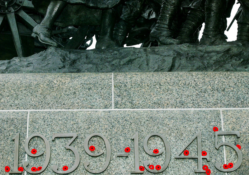 Red poppies are afixed to the World War years below the statues of the War memorial below Parliament Hill in Ottawa, Monday Nov.11, 2002.(CP PHOTO/Fred Chartrand)