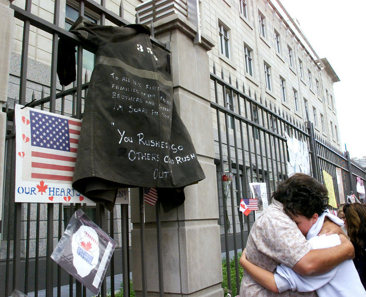 "Retired Ottawa fireman Butch Moore hugs his daughter Brigitte Hayes after hanging his firefighting coat with the message "" TO ALL N.Y. FIREFIGHTERS AND FAMILIES OF THE FALLEN BROTHERS AND SISTERS I'M SORRY FOR YOUR LOSS.   YOU RUSHED IN SO OTHERS COULD RUSH OUT"" on the fence of the United States Embassy in Ottawa Friday Sept 14, 2001.(CP PHOTO/Fred Chartrand)"