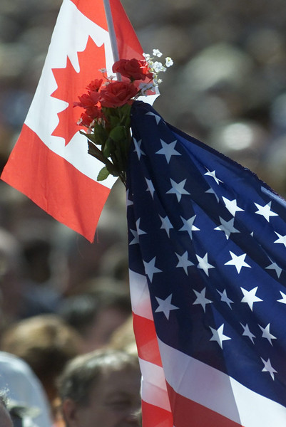 Flags of the United States and Canada were held together during a National Day of Mourning ceremony in Ottawa on Friday Sept. 14, 2001.  Up to 80,000 tourists, government workers, expatriate Americans and others stood shoulder to shoulder on the front lawn of Parliament and bowed their heads for three minutes of silence. (CP PHOTO/Fred Chartrand)