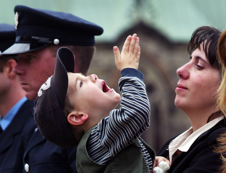 Marie Claude Tanguay looks on as her three-year-old son Felix Antione Lacoste  blows a kiss skyward in memory to his father, Insp. Andre Lacoste of Montreal,  who killed on duty, during a memorial ceremony for firefighters killed in the line of duty on Parliament Hill in Ottawa, Sunday,  September 12, 2004.(CP PHOTO/Fred Chartrand)