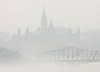 Parliament Hill is seen from across the Ottawa River in Gatineau, Quebec, with the Alexandria interprovincial bridge, below, covered in fog as mild weather hits the capital area, Wednesday, March 14, 2007.(CP PHOTO/Fred Chartrand) CANADA