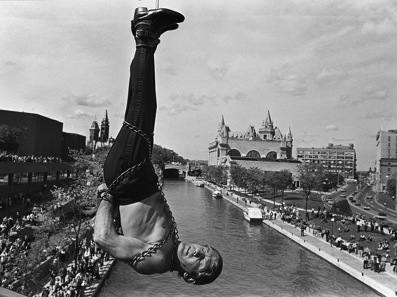 "Magician Allan Allan performs his ""Houdini act"" as he attempts to free himself from chains before the burning rope gives way.  Allan managed to escape in the nick of time saving himself from the fall to the Rideau Canal in Ottawa on September 10, 1975.   Fred Chartrand/The Canadian Press"