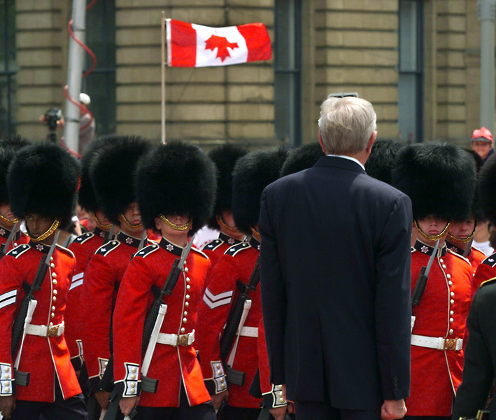 Governor General Romeo LeBlanc watches the Governor General Foot Guards march past while a Canadian flag flies mistakenly upside down in the crowd during Canada Day ceremonies on Parliament Hill in Ottawa on Thursday, July 1, 1999.    Fred Chartrand/The Canadian Press
