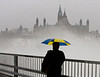 A pedestrian crosses the inter-provincial bridge crossing Ottawa and Gatineau, Quebec, Tuesday January 8, 2008 as fog rises around Parliament Hill with rain and above seasonal temperatures, climbing to 10 C .   Fred Chartrand/The Canadian Press