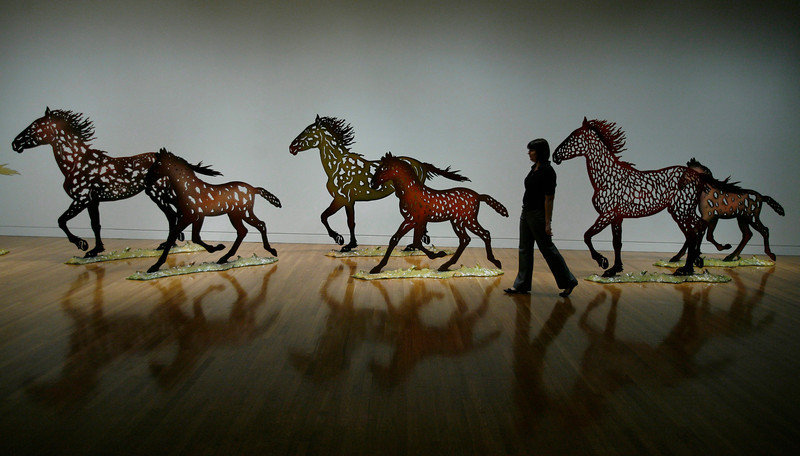 Julie Langelier of the National Gallery of Canada walks past a herd of galloping horses titled Running Horses by Canadian sculptor Joe Fafard, Monday February 11, in Ottawa. The major retrospective is on display at the National Gallery until May 2008.  Fred Chartrand/The Canadian Press