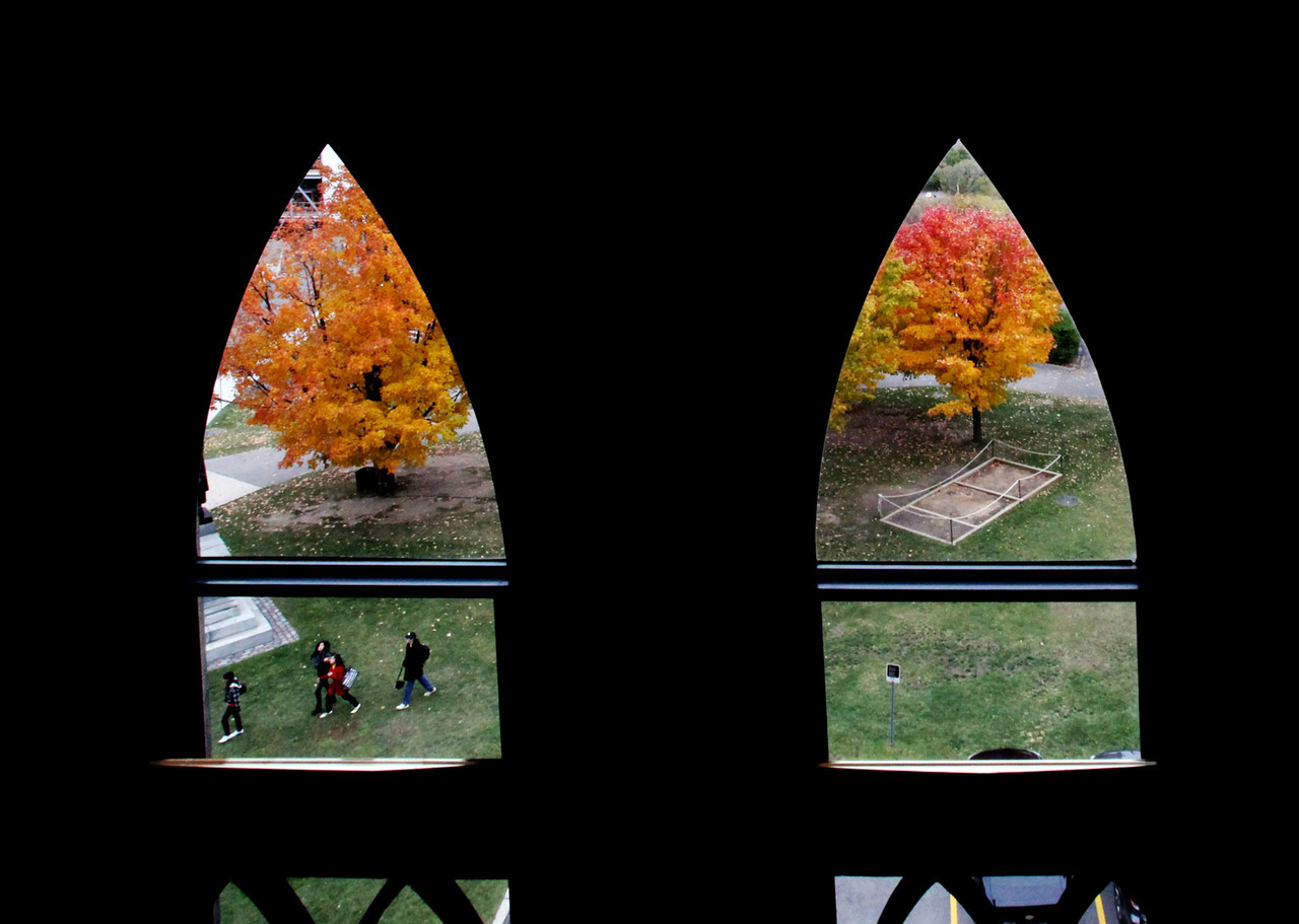 Viewed through windows of the Parliament Buildings in Ottawa a group of students walk around the Fall colours on Parliament Hill, Wednesday October 21, 2009. THE CANADIAN PRESS/Fred Chartrand