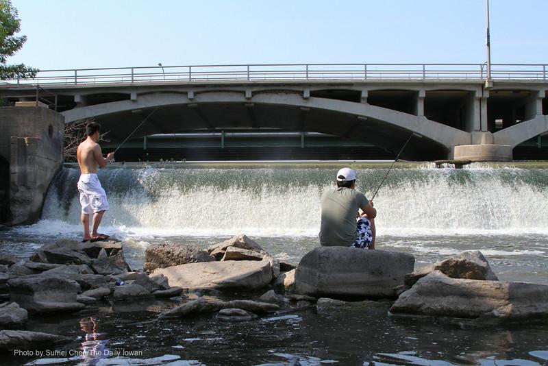 Iowa City, Iowa- Yi Wei Zheng (right) and Jimmy Le fish near the Burlington Street Dam on Sunday, July 1, 2012. The Burlington Street Dam may be turned into a recreation facility in the coming years. (The Daily Iowan/Sumei Chen)