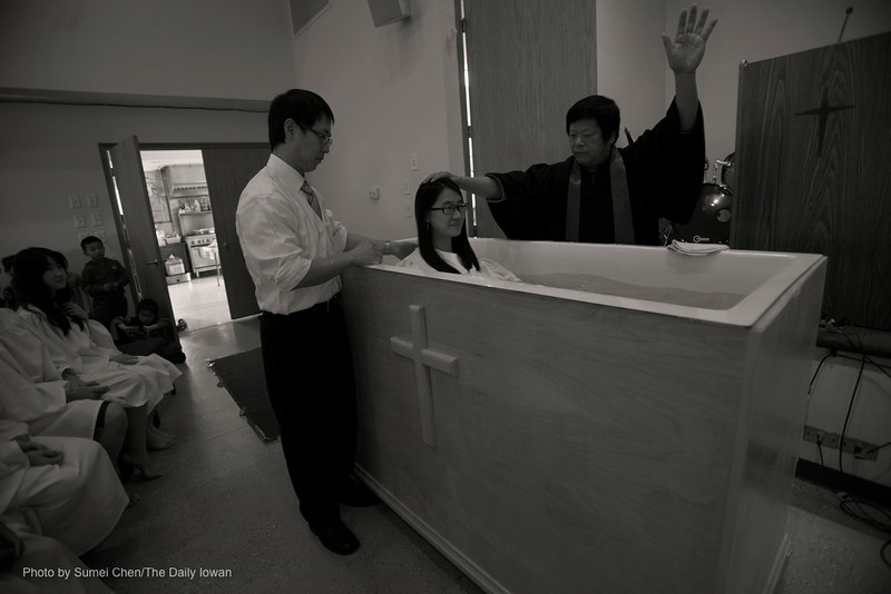 Pastor Wen-Yau Hsieh baptizes UI student Yahong Ding in the Chinese Church of Iowa City in Iowa City, Iowa on Sunday, 25, 2012. Eight people got baptized in that morning. This church provides service of baptism around Easter and Thanksgiving every year. (The Daily Iowan/Sumei Chen)