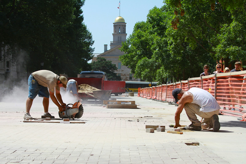 Iowa City, IA- Belle Plaine Nursery staff, Brett Weisskopf and Lloyd Thede work on replacing broken blocks in T. Anne Cleary Walkway on Wednesday, July 18, 2012. (The Daily Iowan/Sumei Chen)