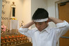 Tom Ta (17) whose mother Mindy Ta parished in the crash August 8th, ties a white head band around his forhead, indicating a mourning family member, before heading to mass.
