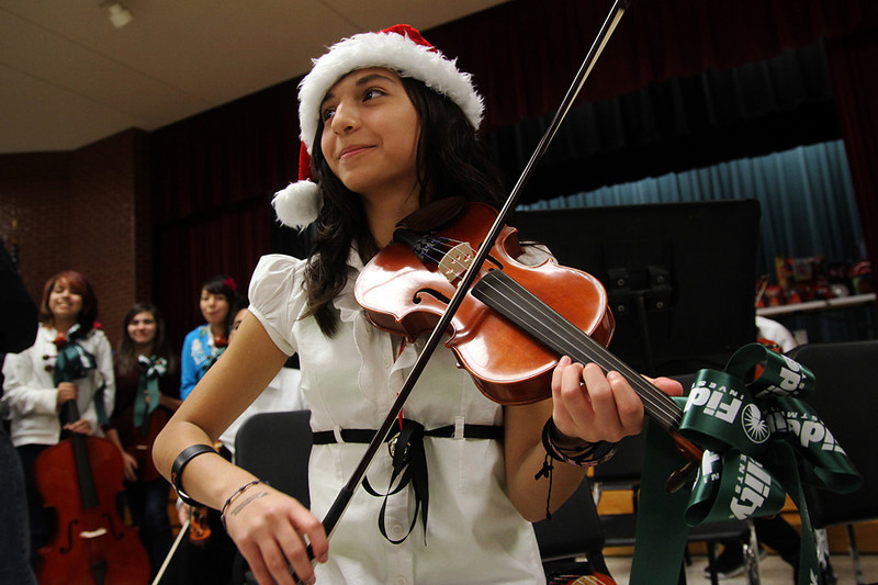 A student tries out her new violin. Fidelity Investments donated $28,000 worth of musical instruments to South Houston Intermediate School. Photo by Pin Lim.