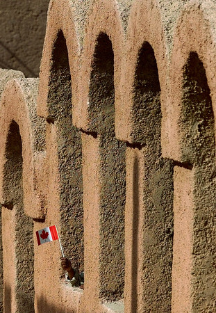 A Palestinian Refugee waves a Canadian flag through a fence at the Souf Palestinian Refugee Camp in Jerash, Jordan, that Prime Minister Jean Chretien toured, Sunday, April 16, 2000.(CP PHOTO/Fred Chartrand)