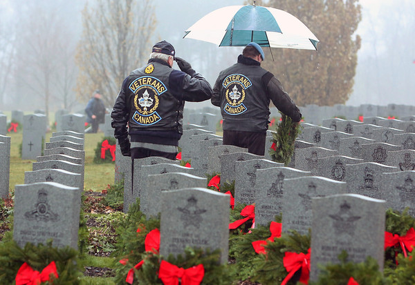 A veterans salutes as another places a wreath at headstones of fallen soldiers during a Wreaths Across Canada ceremony at Beechwood Military Cemetery in Ottawa, Sunday December 2, 2012. The commemorative ceremony has chosen to place a wreath on the headstone of every veteran buried in the National Military Cemetery, the first Sunday of every December at 1:30, Beechwood Cemetary, Ottawa. . THE CANADIAN PRESS/Fred Chartrand