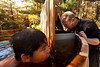 10/11/10 Phillipston, MA -- WIth Mateo Gold, 7, looking on, Frank Rudy Schaeffer adds wood to the stove in their wood-fired hot tub in Phillipston, Mass. Oct. 11, 2010.  Erik Jacobs for the New York Times