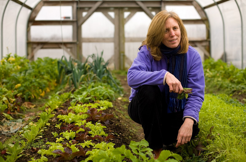 """1/17/08 Chilmark, MA -- Portrait of Jan Buhrman in the greenhouse of her friends Mitch Posin and Clarissa Allen in Chilmark, MA.  Surrounding Buhrman is a mix of """"hearty salad greens"""" which grow through the winter on the 100-acre Allen Farm.  Buhrman tries to only eat what is locally produced on Martha's Vineyard, where she lives year-round.  January, 17 2008.  Erik Jacobs for the New York Times"""