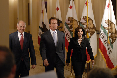 Governor Arnold Schwarzenegger leads exiting State Supreme Court Chief Justice Ron George and incoming Chief Justice Tani Cantil Sakauye to the podium in the capitol building in Sacramento, Ca.