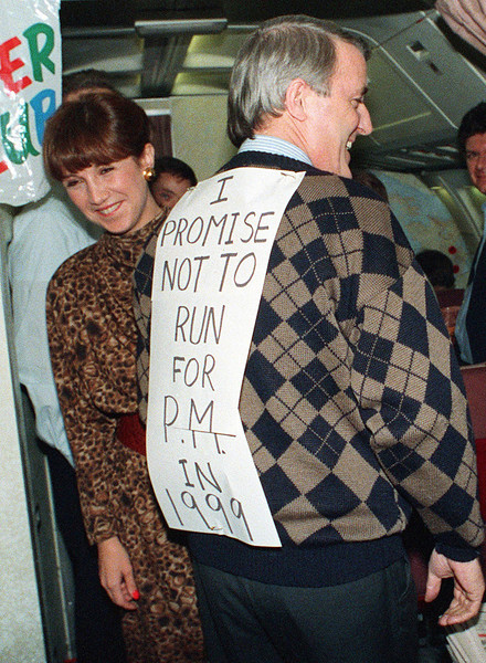 Prime Minister Brian Mulroney, supported by his wife Mila, jokes with the media trevelling on his campaign plane Nov. 22, 1988 during the flight home to Ottawa from  Baie Comeau.  Mulroney wore the sign that said he would not run in 1999, a response to questions earlier in the day regarding his intentions for a third term of office.