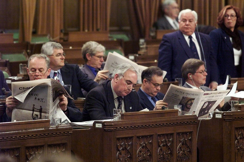 After sitting through Tuesdsay night some members of Parliament read newspapers in between votes while other stand to be counted in the House of Commons, Wednesday, December 8, 1999. Parliament sat through last night voting on a tower of Reform party amendments dealing with the Nisga'a land-claim treaty legislation.<br /> (CP PHOTO/Fred Chartrand)