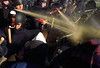 RCMP riot squad members douse protesters with pepper spray as they try to break through police lines on Parliament Hill, Wednesday, November 17, 1999.  About 300 people demanding federal money for low-income housing confronted about 100 RCMP  - some equipped with helmets, shields and batons  - near the Peace Tower. (CP PHOTO/Fred Chartrand)